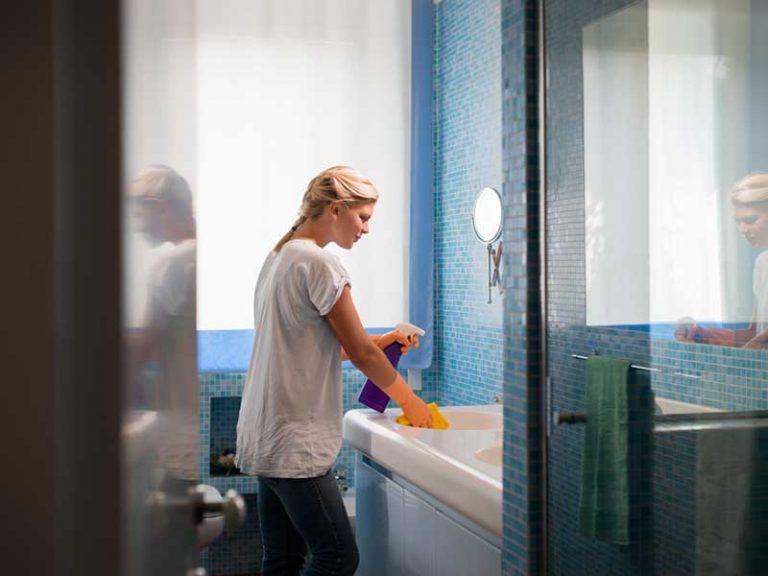 Οικιακή βοηθός καθαρίζει καθρέπτη σε τουαλέτα