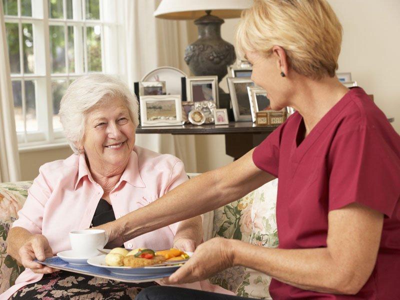 Νεαρή γυναίκα σερβίρει φαγητό σε ηλικιωμένη γυναίκα.