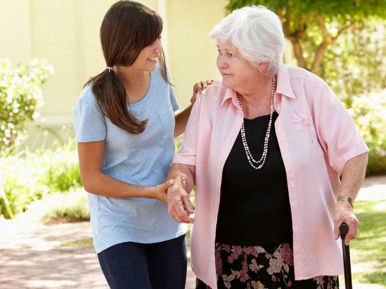 Νεαρή γυναίκα συνοδεύει ηλικιωμένη σε περίπατο